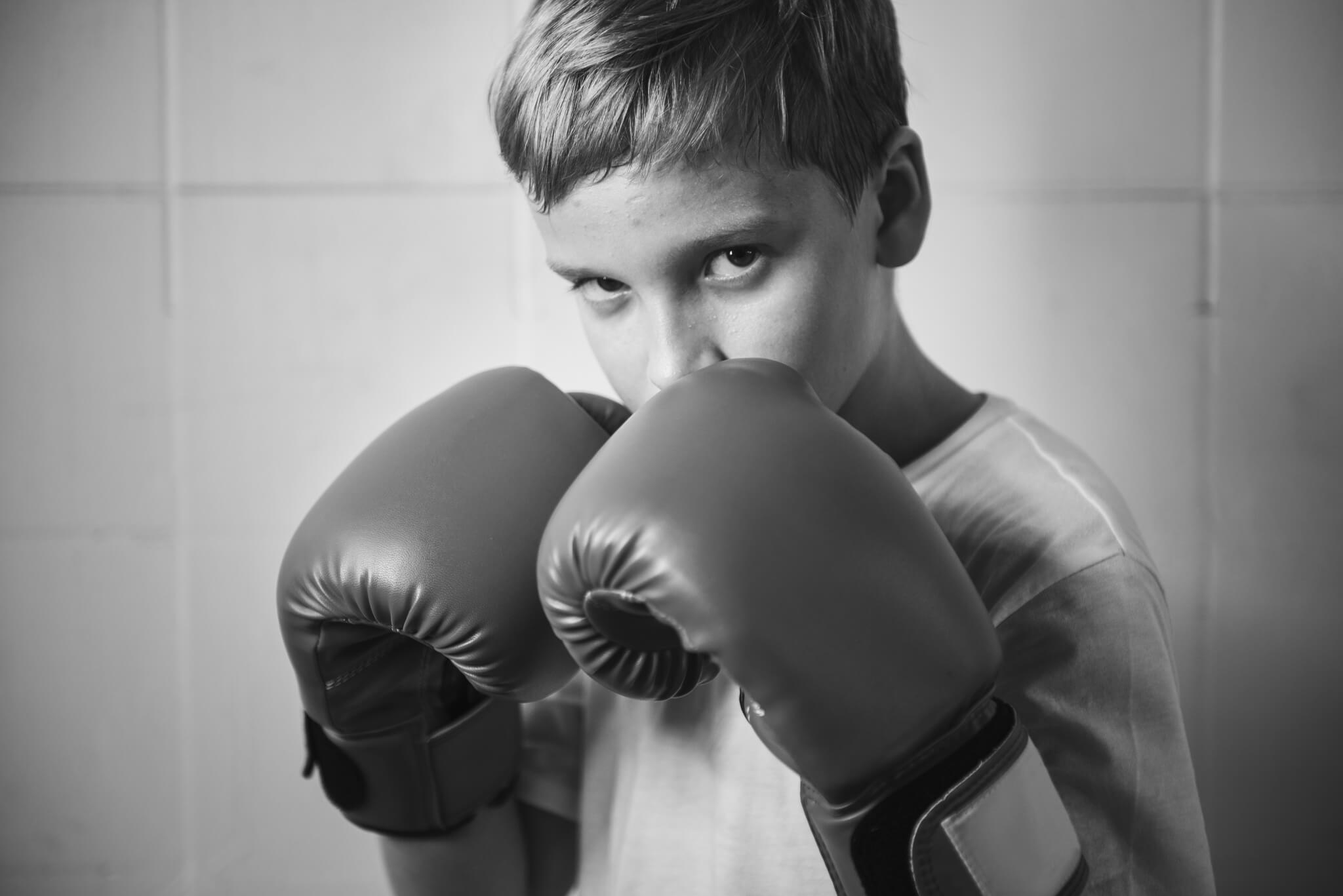 determined child wearing boxing gloves